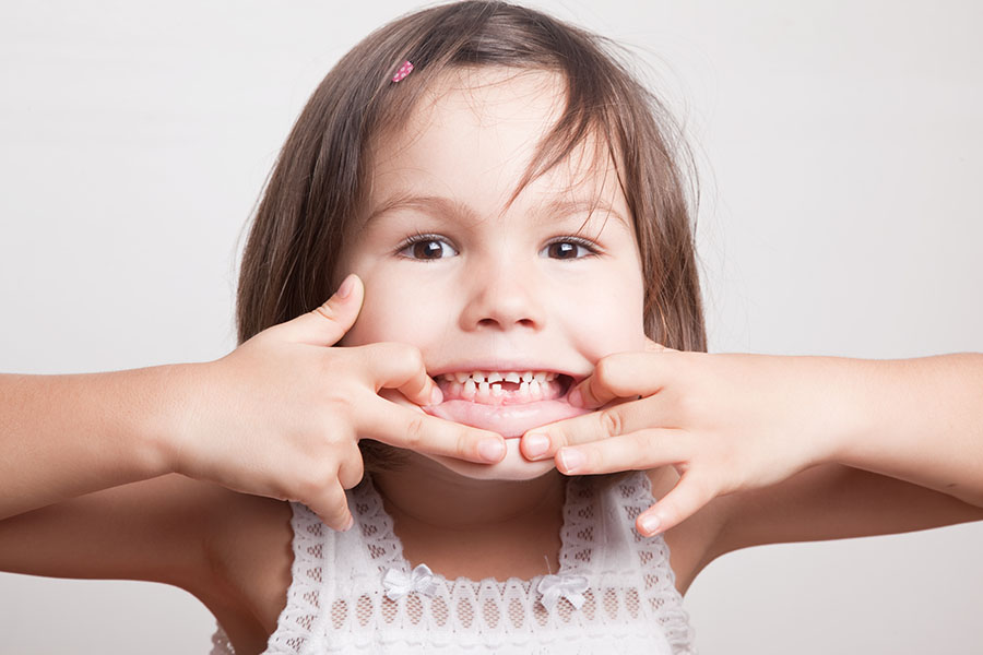 child widened her smile with her hands